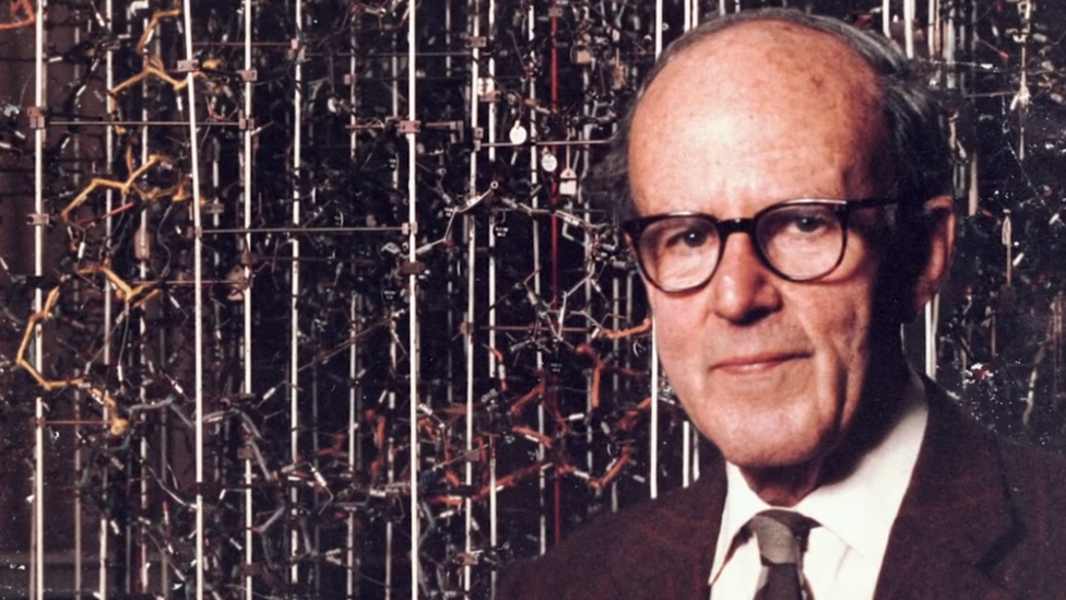 Max Perutz frente a un modelo de una estructura molecular