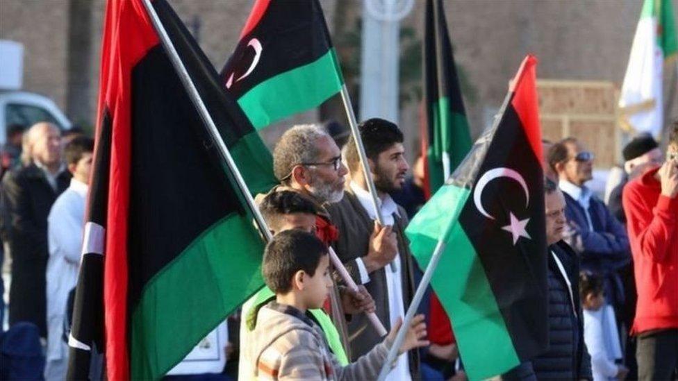 أشخاص يحملون علم ليبيا