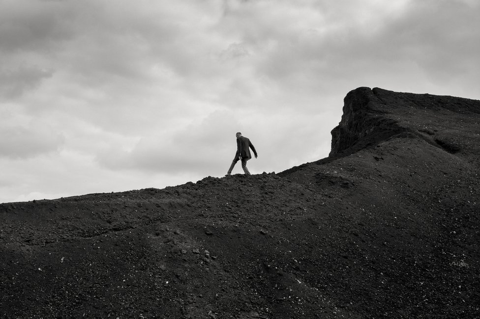 A man stands on the peak of a hill
