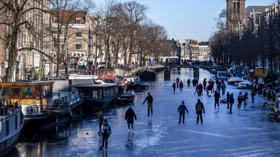 Skaters gather on ice on the canals in Prinsengracht, Amsterdam on February 13, 2021.