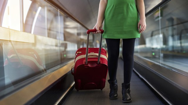 Woman with suitcase on moving airport walkway