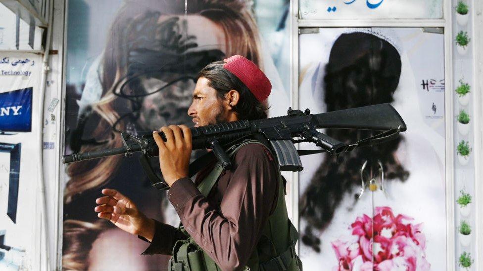 Un combatiente talibán pasa junto a un salón de belleza con un arma M16.