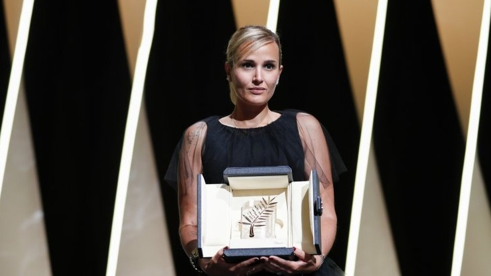 Director Julia Ducournau posing with the award on stage