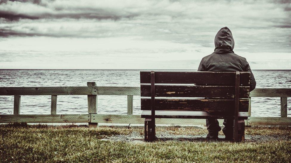 Hombre sentado solo en una banca.