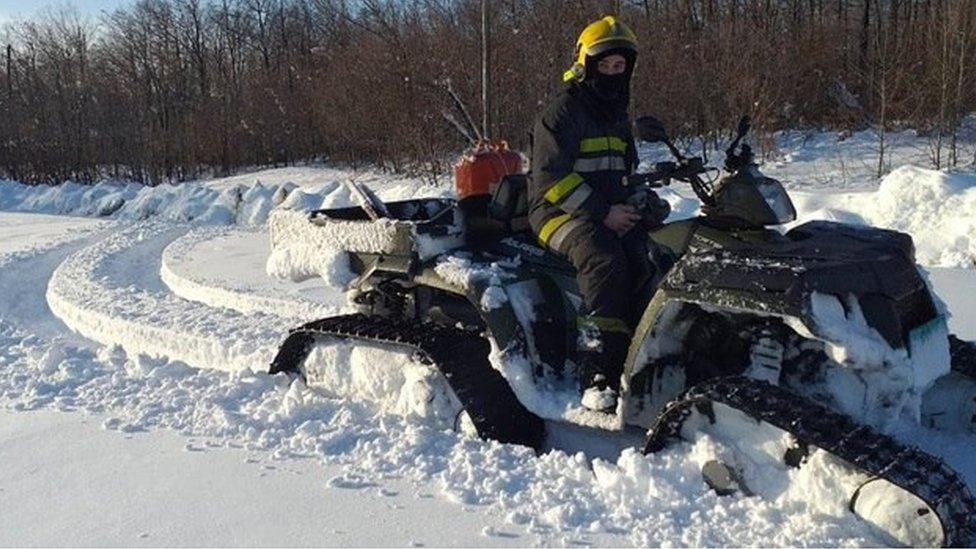 Radnik zadužen za čišćenje snega na mašini za čišćenje zaglavljen u snegu.