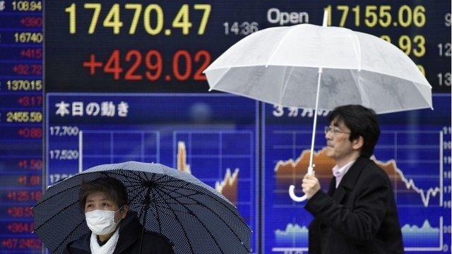 Pedestrians walk past stock market boards