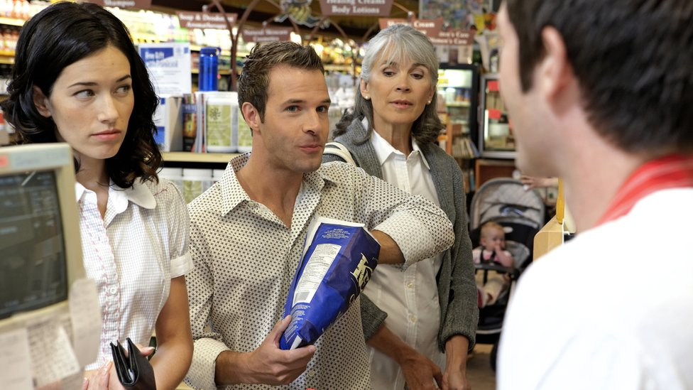 Fila de personas para pagar en un supermercado.