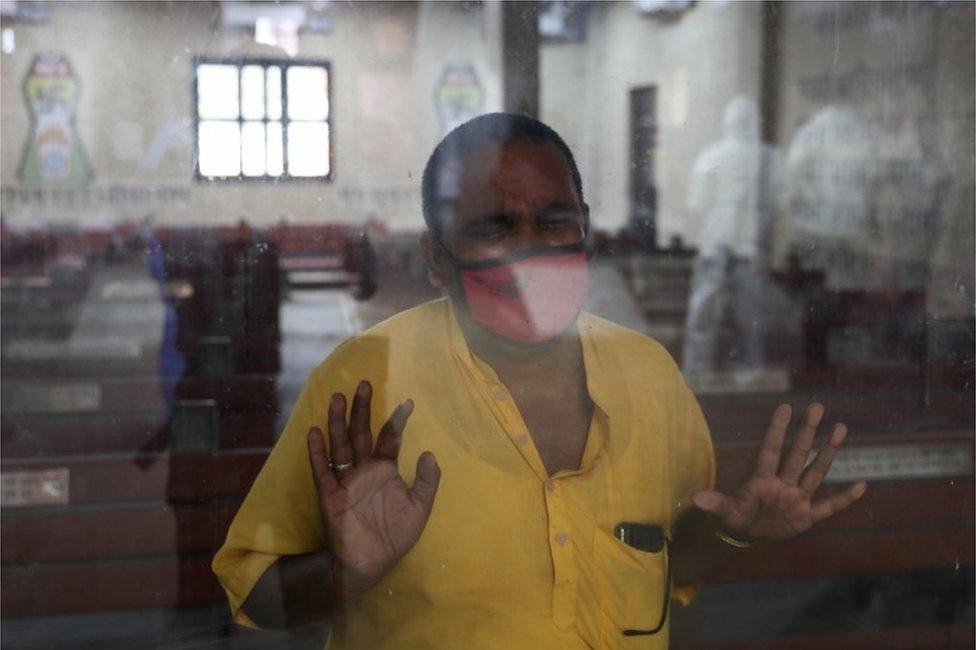 El pariente de un familiar que murió de coronavirus observa a través de una ventana cómo preparan a la víctima para su cremación en Nueva Delhi, India, 9 de abril de 2021