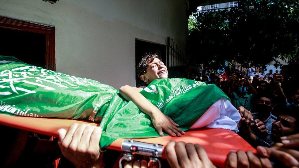 Un niño palestino se aferra al cuerpo de una víctima durante un funeral