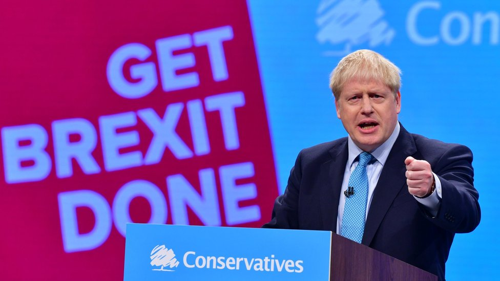 """Boris Johnson at Conservative Party Conference in front of """"Get Brexit Done"""" sign"""