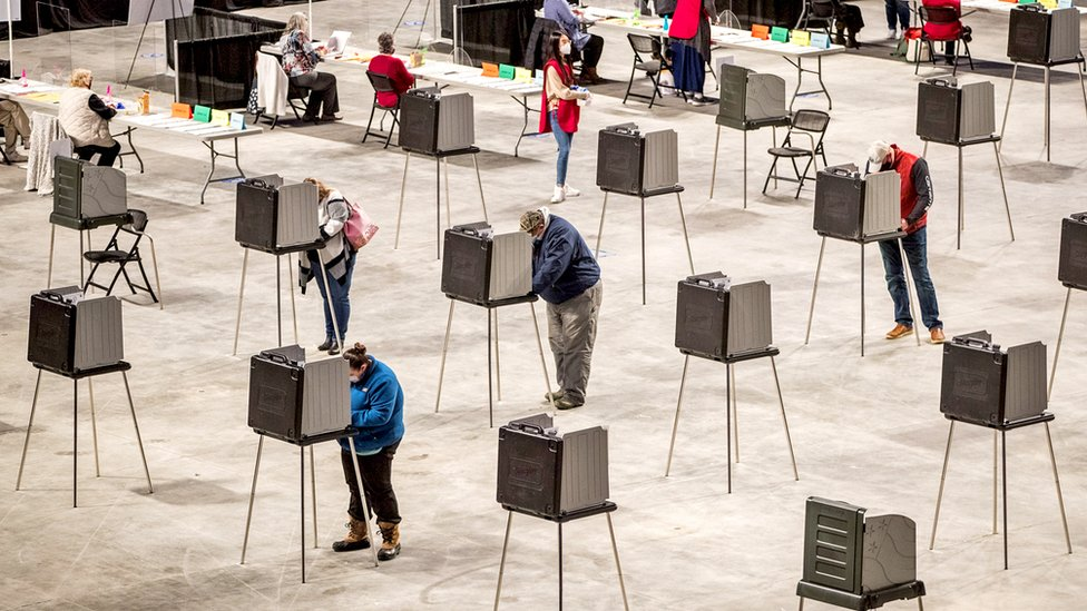 Voters fill out and cast their ballots at the Cross Insurance Center polling location in Bangor, Maine