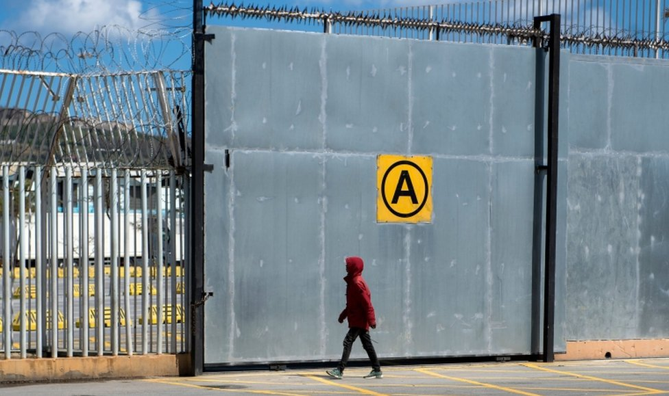 A young Moroccan walks toward a fence at the harbour of the port city of Ceuta