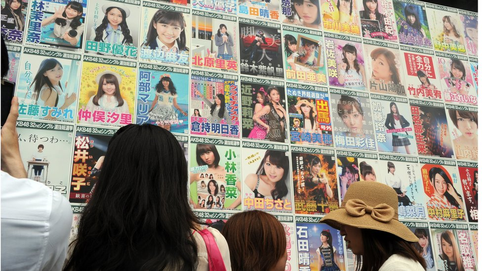 Japanese girls pop group AKB48 fans look at the election campaign posters prior to the group's general election announcement at the Yokohama stadium in Yokohama, south of Tokyo on 8 June 2013.