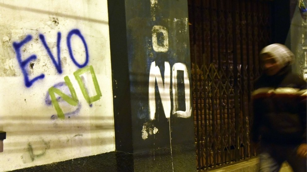 """A man is seen walking next to a graffiti that reads """"Evo no"""" after the referendum in El Alto, Bolivia, on 21 February 2016"""
