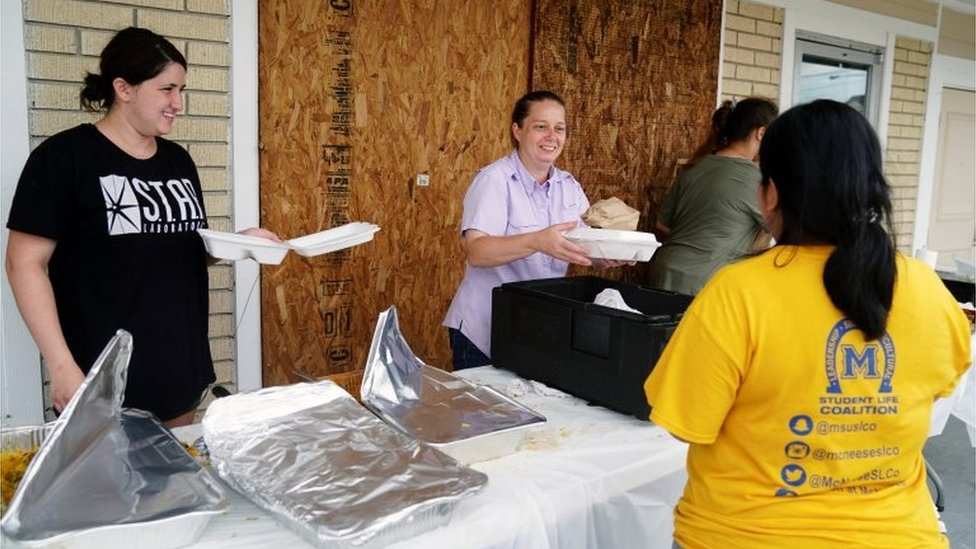 Amanda Abassi, center, serves free hot food to community members with her daughter and extended family in front of her restaurant Royal Tandoor after Hurricane Laura passed through the area in Lake Charles, Louisiana, U.S. August 28, 2020