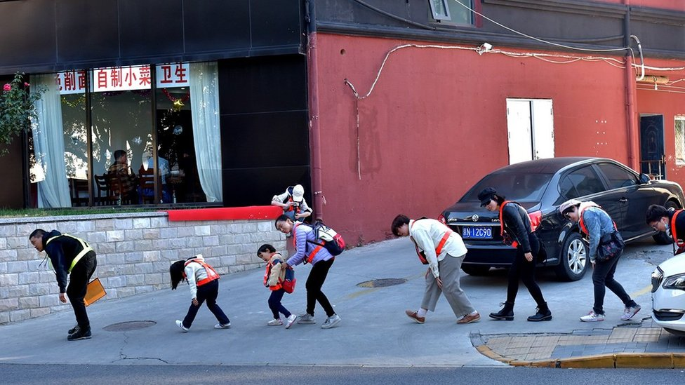 為了躲避攝像頭,鄧玉峰和幾名參與者在幸福大街上彎腰前行。