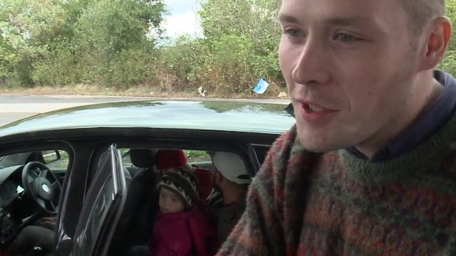 British PhD student Oliver with a Syrian family inside a car in the background