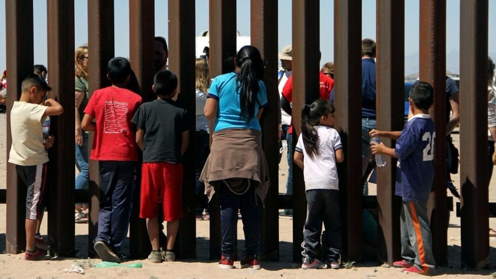 Children look through the US-Mexico border wall