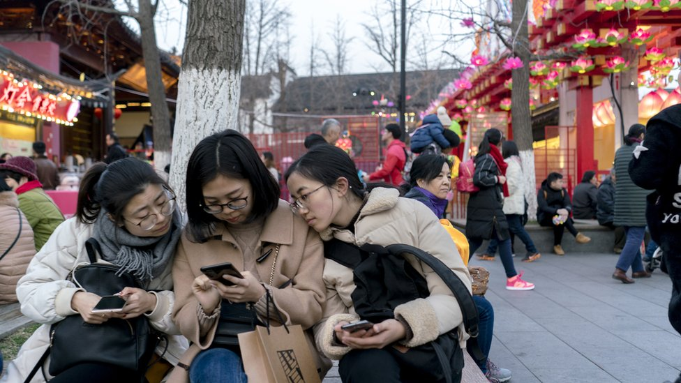 Women in China look at smartphones
