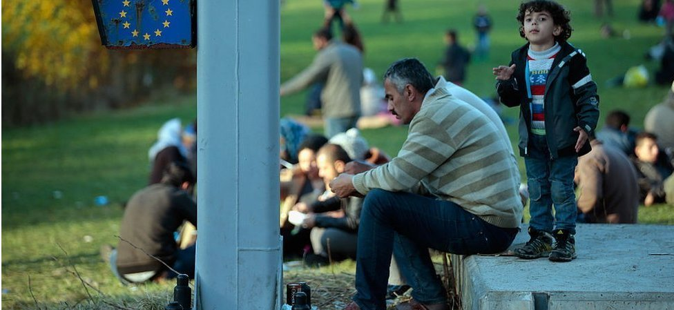 Migrants take a rest after arriving with buses at the border to Austria on October 28, 2015 near Wegscheid, Germany