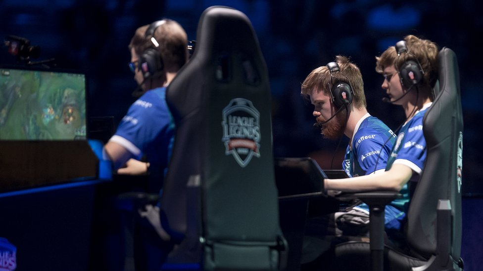 Three male gamers compete in an esports game called League of Legends