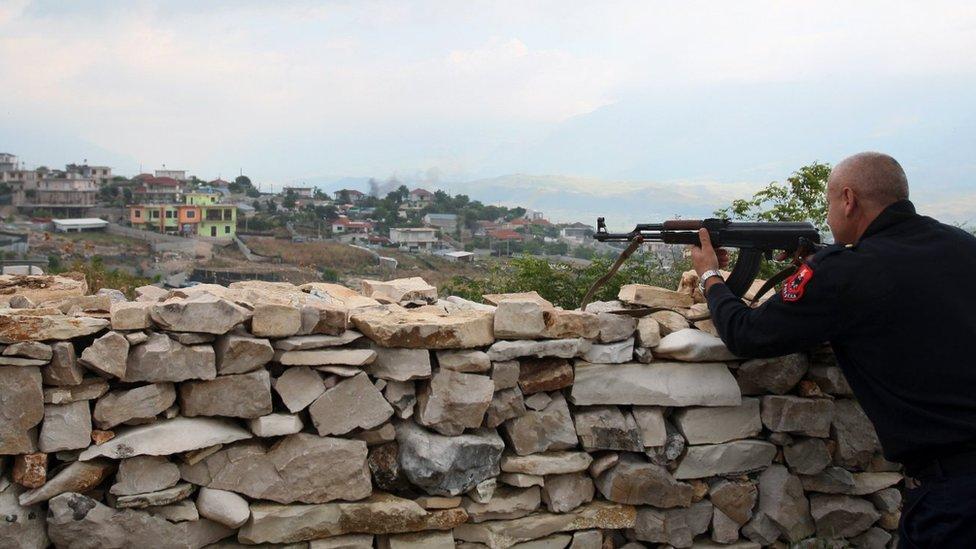 Un oficial de policía albanesa asegura el perímetro de una casa en Lazarat, un pueblo conocido como la capital europea del cannabis, al sur de la capital albanesa Tirana, el 18 de junio de 2014