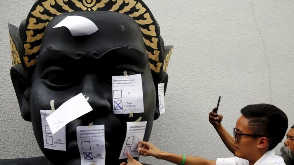 "An opposition student attaches a mock ballot with the option ""No"" to a statue during a protest against the military-backed draft constitution in Bangkok"