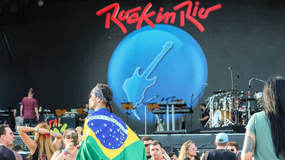 Man wrapped in Brazilian flag in front of a stage at Rock in Rio.