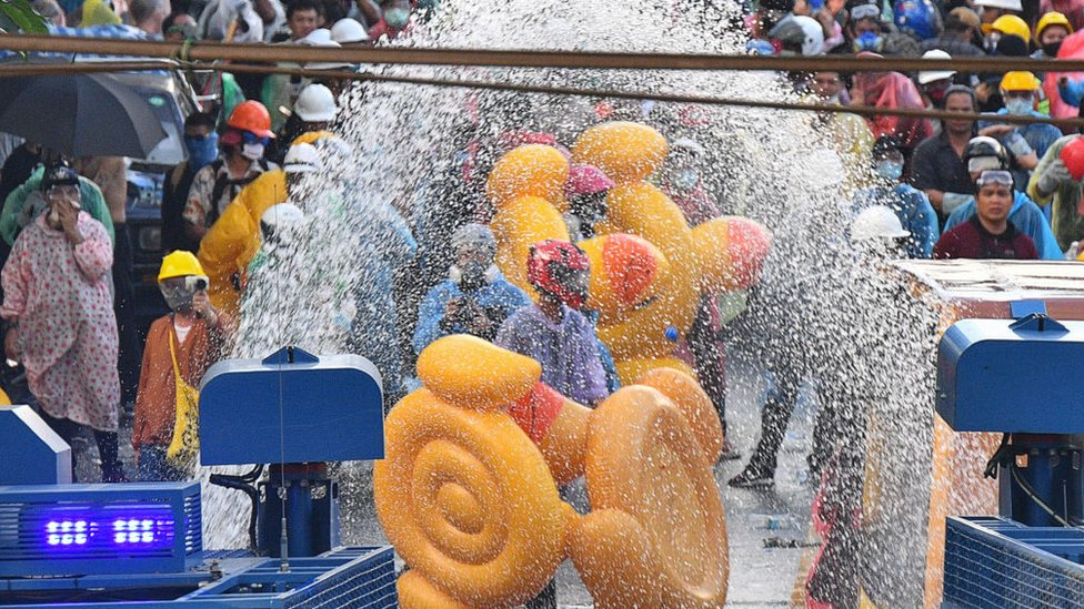 Demonstrators use inflatable rubber ducks as shields to protect themselves from water cannons during an anti-government protest in Bangkok, Thailand, 17 November 2020
