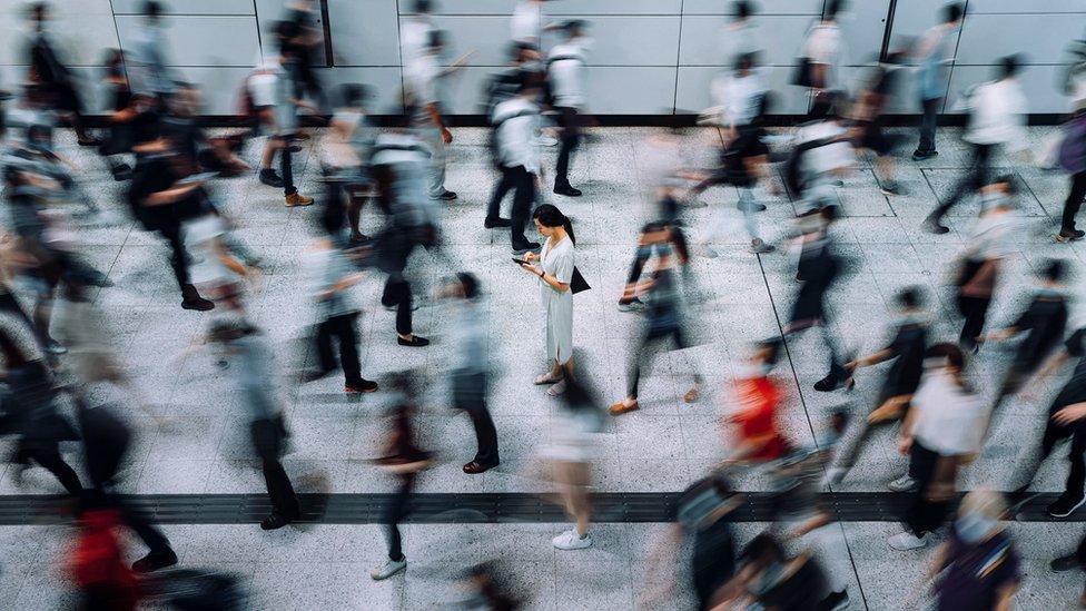 Uma jovem mulher em foco nítido, usando smartphone, cercada por passageiros embaçados, correndo em uma estação subterrânea durante os horários de pico