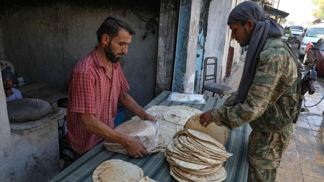 Un combatiente sirio compra en un mercado en el noreste del país