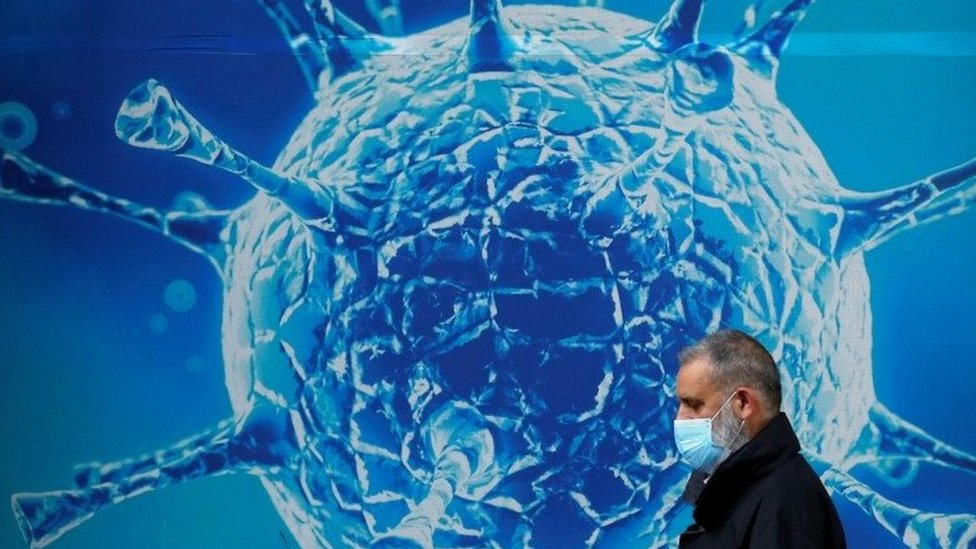 Man wearing a mask walks past an illustration of a virus in Oldham, UK (03/08/20)