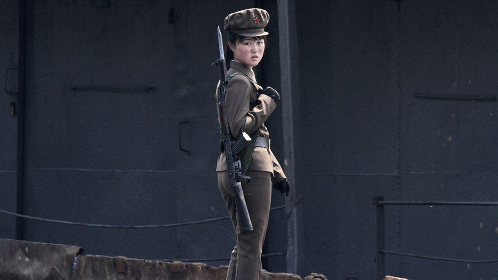 Severnokorejska vojnikinja na obali reke Jalu, u zelenoj uniformi sa puškom na leđima gleda u kameru (2014)