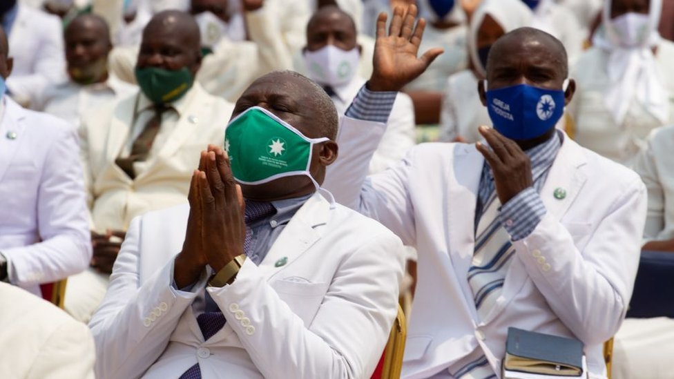 Members of the congregation raise their hands in prayer at the Church of Our Lord Jesus Christ In the World, in Luanda on September 20, 2020.