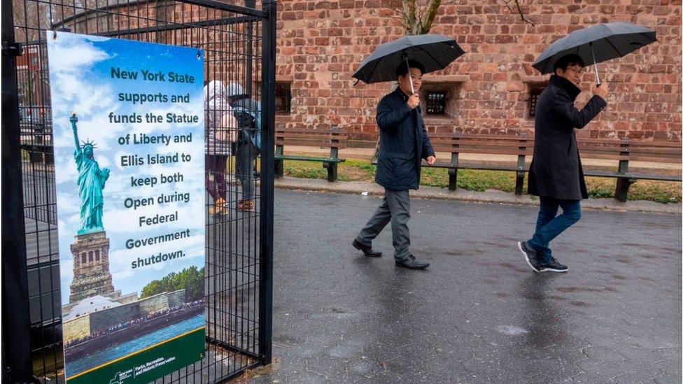 Personas caminando cerca de la Estatua de la Libertad y la Isla de Ellis
