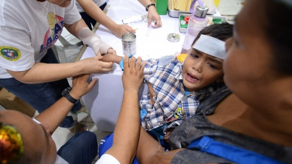 A health worker treats a boy suffering from dengue fever in Cabatuan, Philippines last month