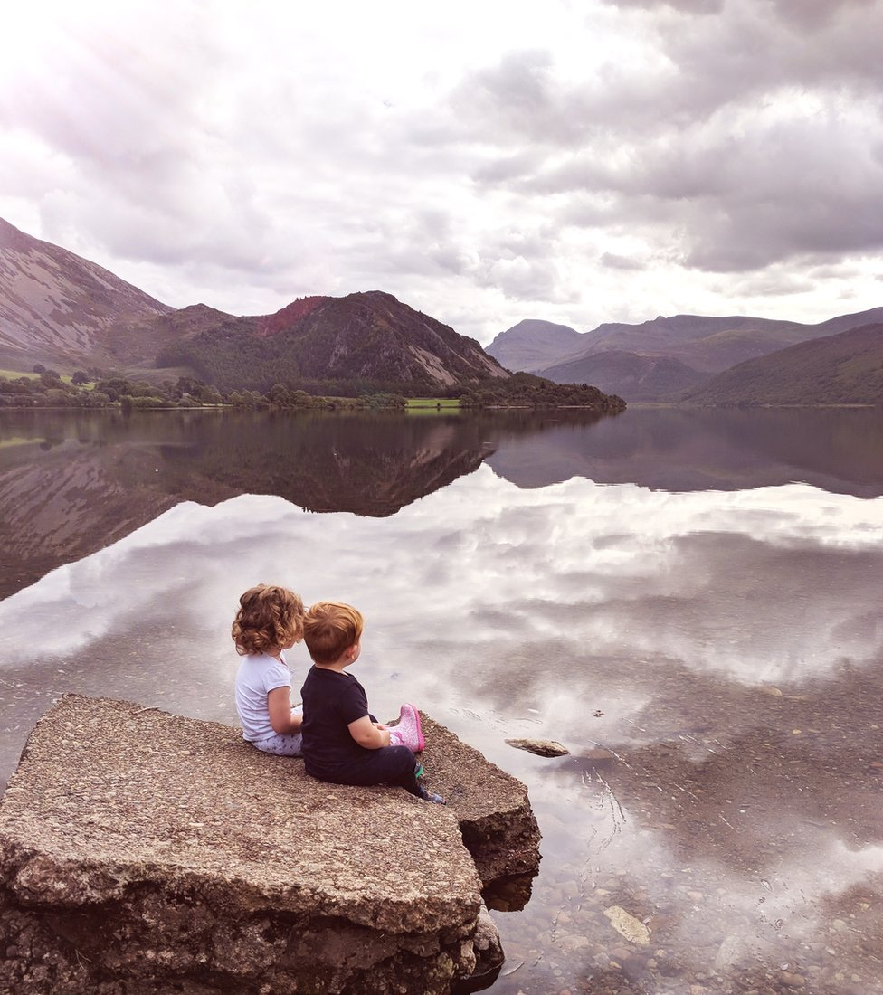 Two children sat by water