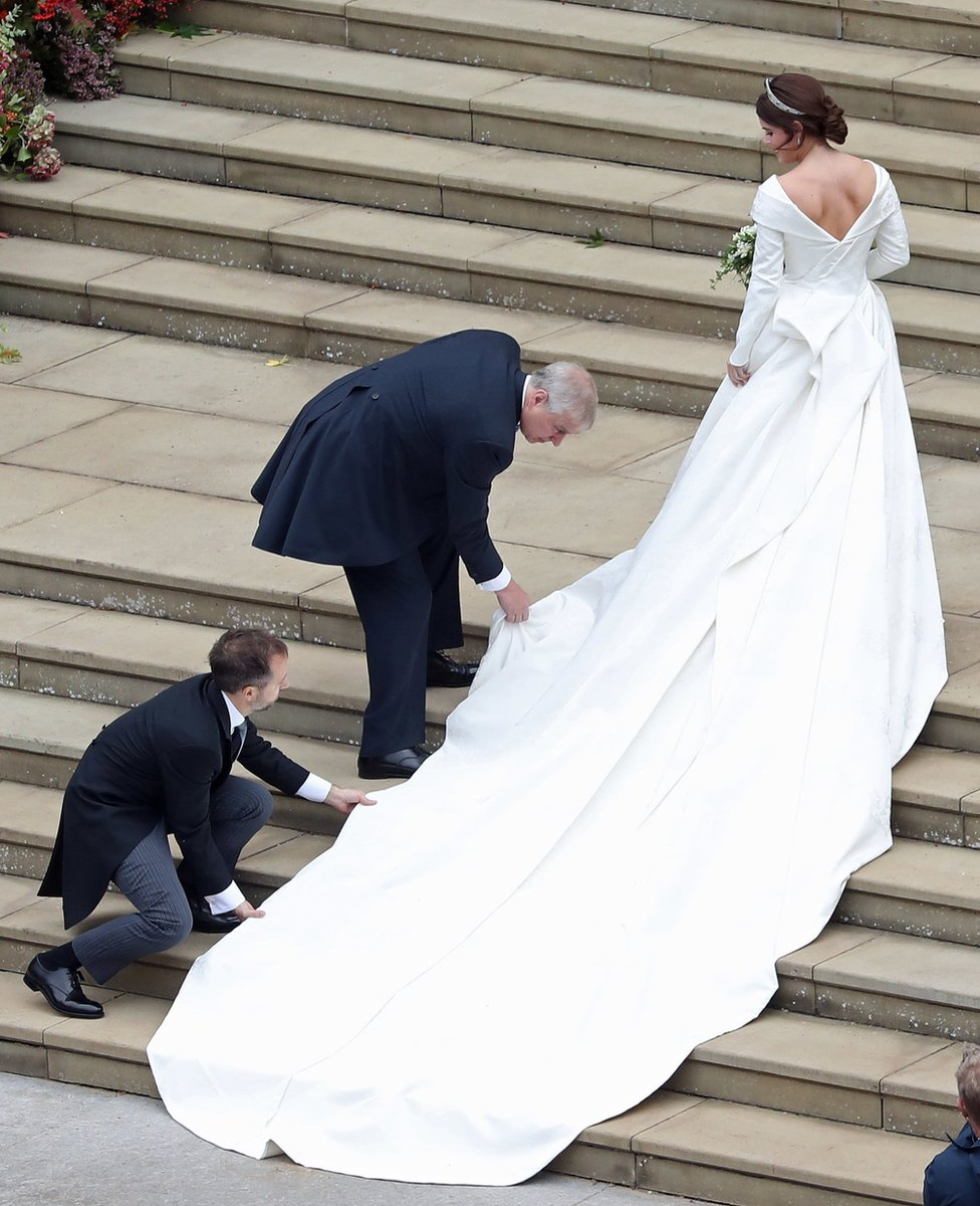 Princess Eugenie of York receives help with her train from her father Prince Andrew