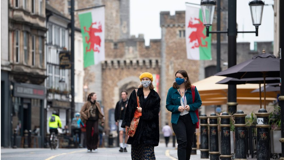 Two women wearing facemasks walk down St Mary's Street