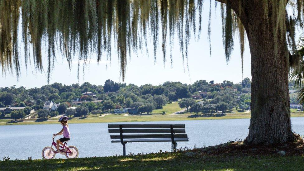 Niña en bicicleta en un parque de Estados Unidos