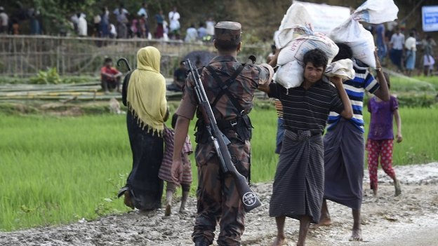 A Bangladesh border guard attempts to clear Rohingya Muslim refugees off a road near a refugee camp