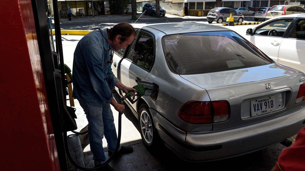 Un hombre llenando el tanque de gasolina de su auto.