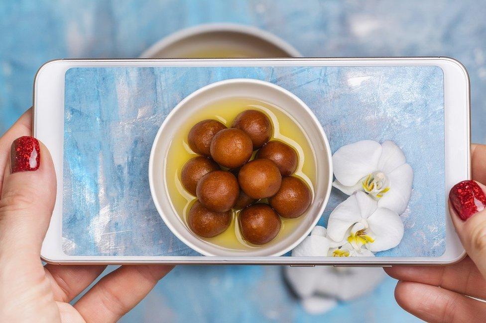 Žena fotografiše porciju gulab jamuna