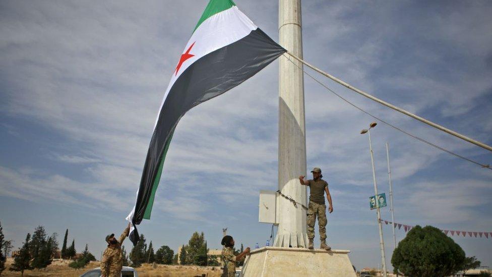 Combatientes sirios alzan bandera en la ciudad de Ayn al-Arus.