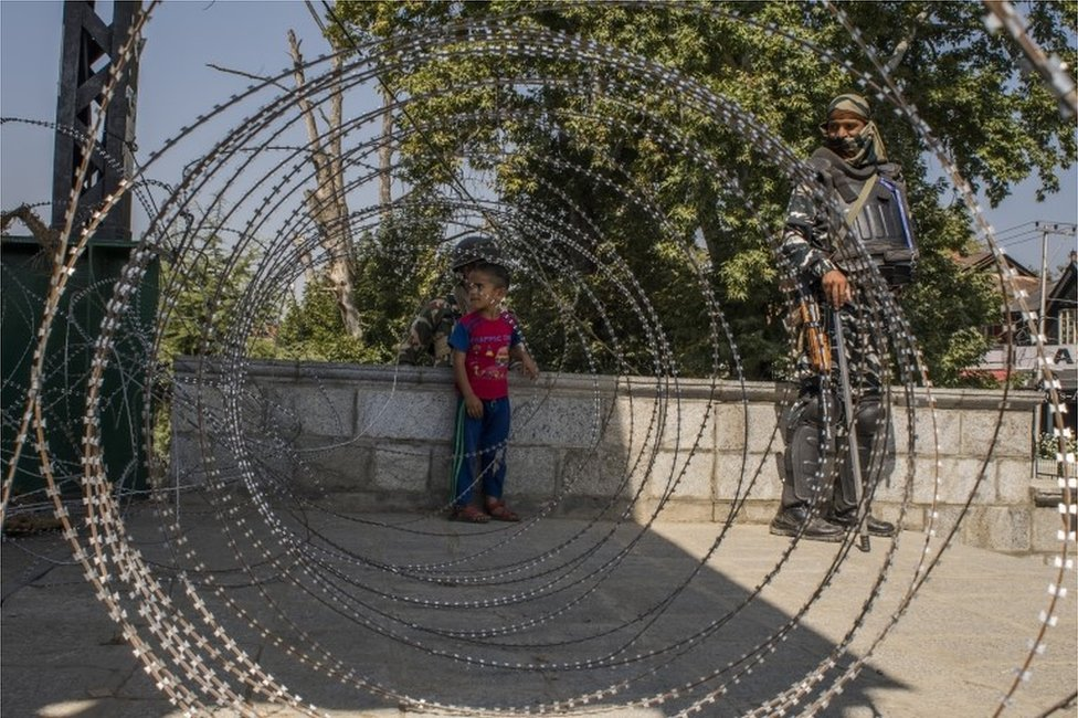 A Kashmir child look towards his parents after he was helped by Indian paramilitary trooper to cross the concertina razor wire laid by Indian government forces during curfew like restrictions, on September 10, 2019 in Srinagar
