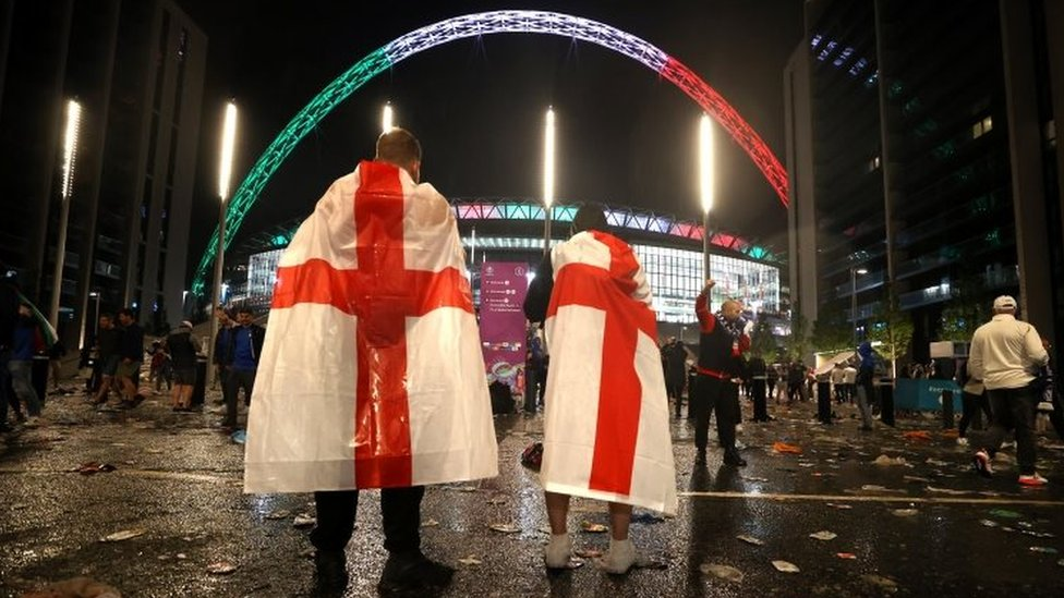England fans draped in national flags leave Wembley stadium in London. Photo: 11 July 2021