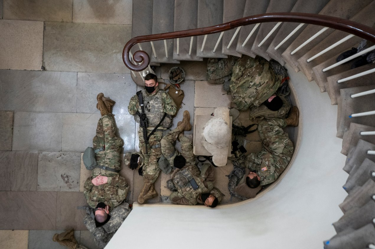 Downward view shows Guardsmen resting by a stairwell