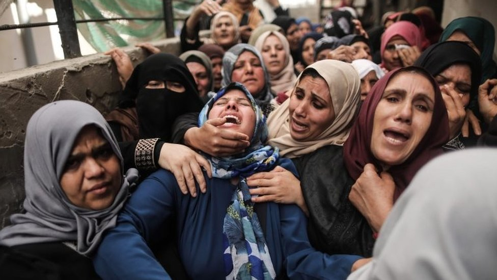 Palestinian relatives of Hamdan Abu Amsha cry during his funeral in Beit Hanun in the northern of Gaza Strip