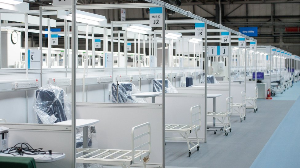 Rows and rows of hospital beds are seen, with parts still wrapped in plastic, in a cavernous space