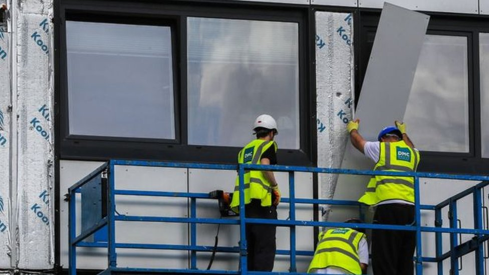 Builders remove cladding from a high rise building